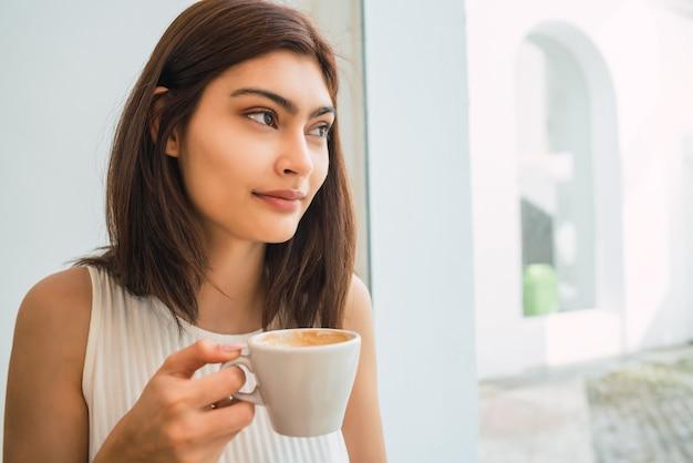Retrato de jovem latina, desfrutando e bebendo uma xícara de café na cafeteria