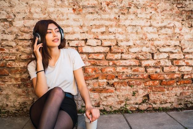 Retrato de jovem latina relaxar e ouvir música com fones de ouvido contra a parede de tijolos. conceito urbano.