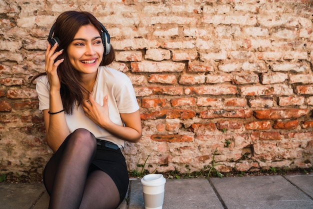 Retrato de jovem latina relaxar e ouvir música com fones de ouvido contra a parede de tijolos.