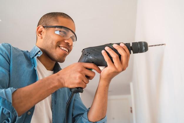 Retrato de jovem latino com uma furadeira elétrica e fazendo um buraco na parede. conceito de design de interiores e renovação em casa.