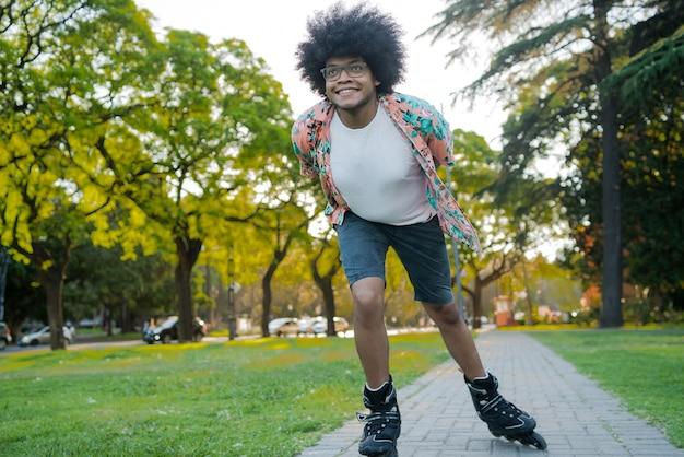 Retrato de jovem latino desfrutando enquanto patins ao ar livre na rua. conceito de esportes. conceito urbano.