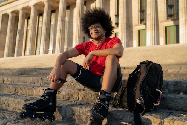 Retrato de jovem latino ouvindo música com fones de ouvido e usando rolos de skate enquanto está sentado ao ar livre. conceito de esportes. conceito urbano.