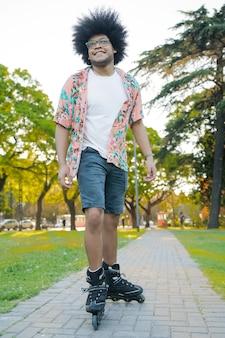 Retrato de jovem latino rollerskating ao ar livre na rua. conceito de esportes. conceito urbano.
