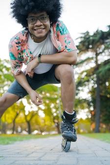 Retrato de jovem latino se divertindo e olhando enquanto patins ao ar livre na rua. conceito de esportes.