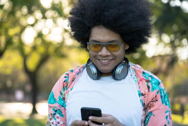 Retrato de jovem latino usando seu telefone celular em pé ao ar livre na rua. conceito urbano