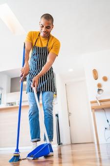 Retrato de jovem latino varrendo o chão de madeira com a vassoura em casa. conceito de limpeza, trabalho doméstico e limpeza.
