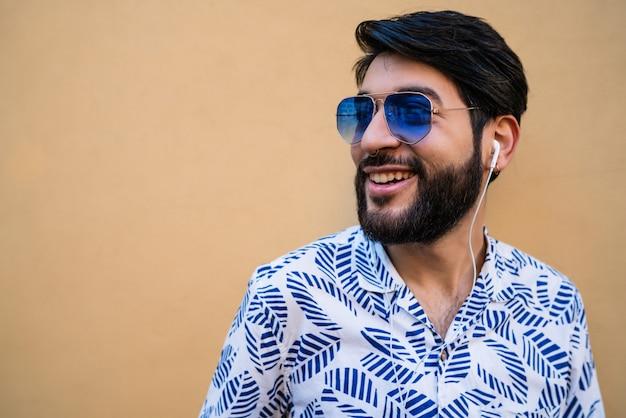 Retrato de jovem latino vestindo roupas de verão e ouvindo música com fones de ouvido contra amarelo.