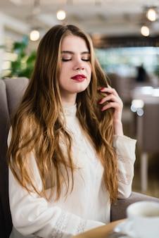 Retrato de jovem linda com maquiagem profissional e penteado no restaurante.