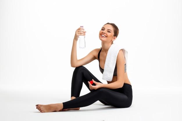 Retrato de jovem linda garota esportiva sobre fundo branco.