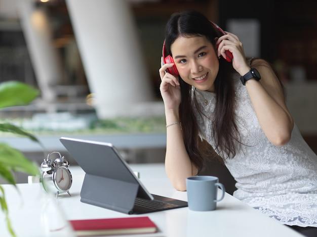 Retrato de jovem linda mulher relaxando com fone de ouvido e tablet no café
