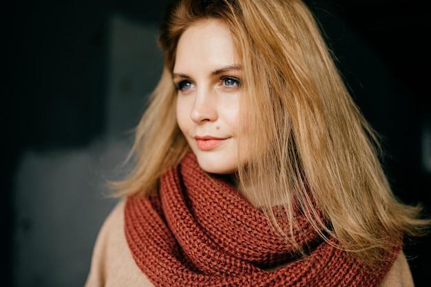 Retrato de jovem loira elegante com lenço vermelho-escuro posando ao ar livre