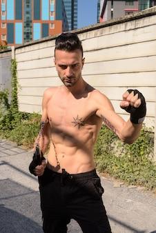 Retrato de jovem lutador bonito com corpo magro e musculoso ao ar livre e tanquinho