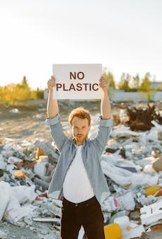 Retrato de jovem lutando pela natureza segurando salvar o sinal da mãe terra no lixão. protestando contra a poluição da natureza, acenando com as mãos pedindo para salvar o planeta.
