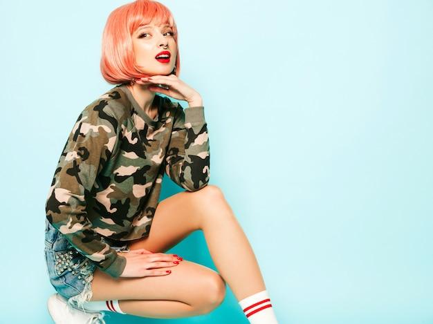Retrato de jovem má hipster linda em roupas da moda vermelho verão e brinco no nariz. mulher sorridente despreocupada sexy sentada no estúdio em peruca rosa perto da parede azul. modelo positivo se divertindo
