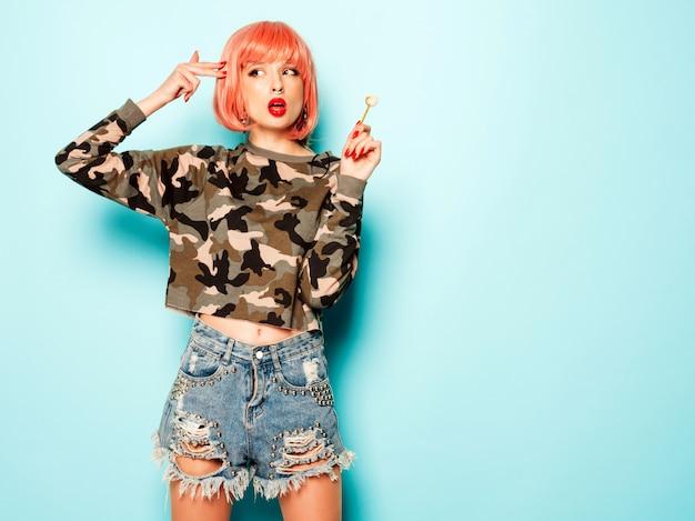 Retrato de jovem má hipster linda garota de short jeans da moda e brinco no nariz. mulher sorridente despreocupada sexy em posando de peruca rosa. modelo positivo lambendo doces de açúcar redondo. faz sinal de arma