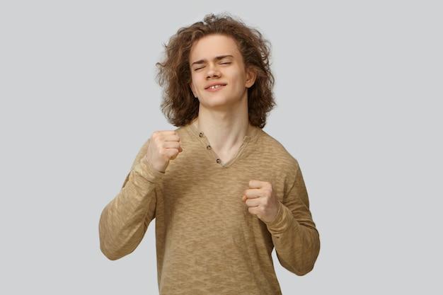 Retrato de jovem macho bonito positivo com cabelos ondulados dançando, mantendo os olhos fechados. cara atraente e emocional sorridente, cerrando os punhos, expressando verdadeira alegria, sendo feliz com boas notícias