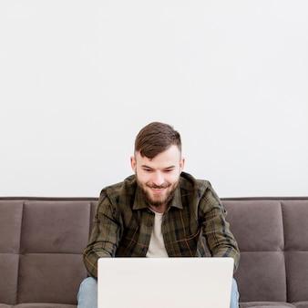 Retrato de jovem macho feliz em trabalhar em casa
