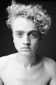 Retrato de jovem magro com cabelo encaracolado sem camisa na cor cinza em preto e branco