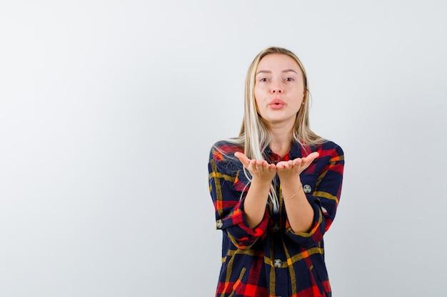 Retrato de jovem mandando beijo com as mãos na camisa e olhando bonita de frente