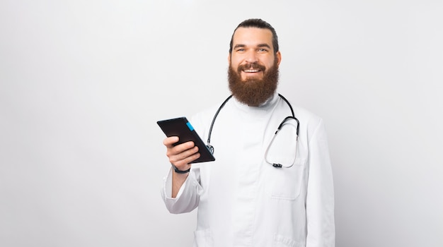 Retrato de jovem médico alegre sorrindo e segurando o tablet