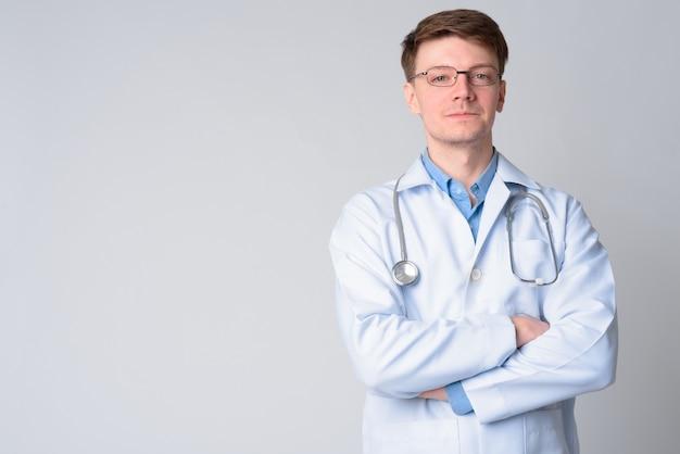 Retrato de jovem médico bonito com óculos, cruzando os braços