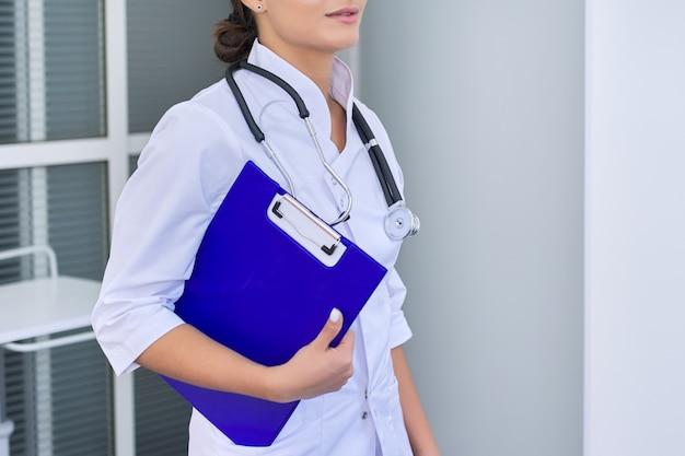 Retrato de jovem médico feminino com a área de transferência do estetoscópio no hospital