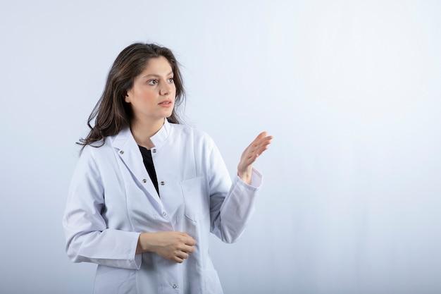 Retrato de jovem médico olhando algo na parede branca.
