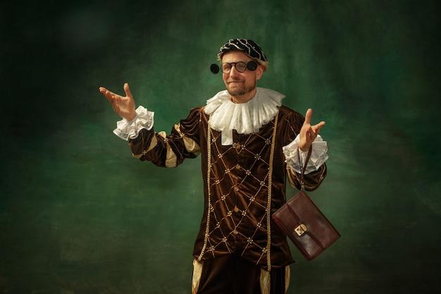 Retrato de jovem medieval em roupas vintage com moldura de madeira na parede escura