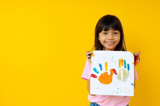 Retrato de jovem menina asiática com arte, criança tailandesa mostra papel de pintura por cor de água com palm e criatividade do conceito de crianças