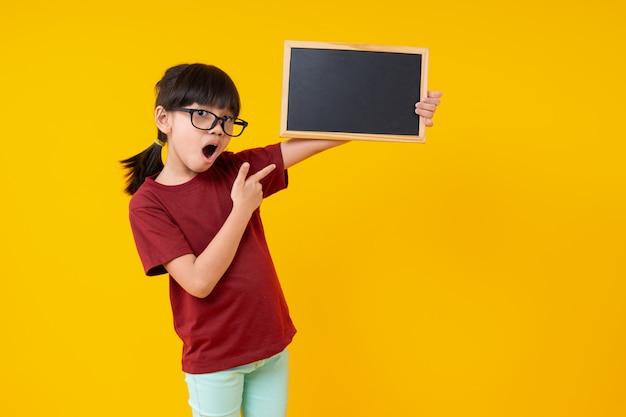 Retrato de jovem menina asiática segurando pequena lousa em branco amarelo