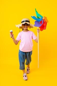Retrato de jovem menina bonita asiática andando e segurando a turbina e sorvete coloridos, criança tailandesa no estilo de verão