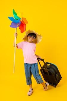 Retrato de jovem menina bonita asiática segurando a turbina colorida e arraste a mala de viagem azul, criança tailandesa no estilo de verão