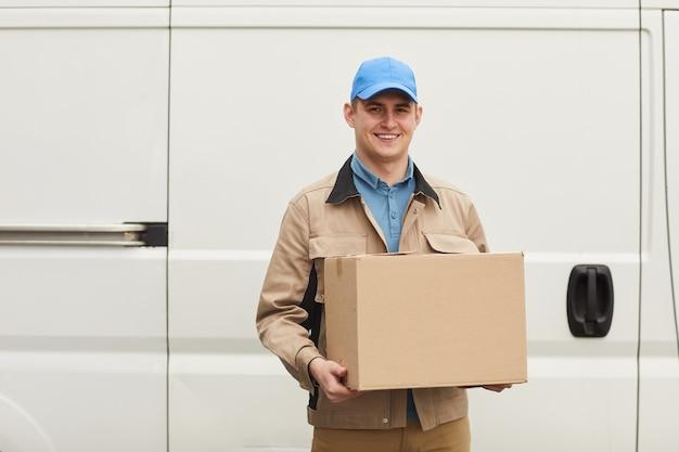 Retrato de jovem mensageiro sorrindo para a câmera enquanto carrega a caixa para fora