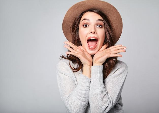 Retrato de jovem modelo elegante animado gritando chocado em roupas de verão casual cinza com chapéu marrom