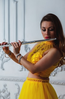 Retrato de jovem modelo no palco vestido amarelo com flauta nas mãos
