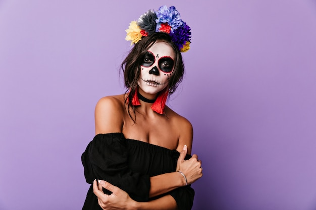 Retrato de jovem morena com coroa de flores multicolorida. mulher com máscara de esqueleto parece misteriosamente