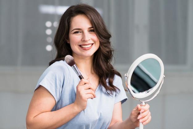 Retrato, de, jovem, morena, com, escova maquiagem, e, espelho