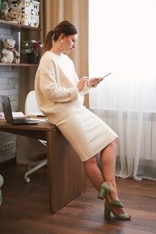Retrato de jovem morena freelancer trabalhando em casa em tablet digital