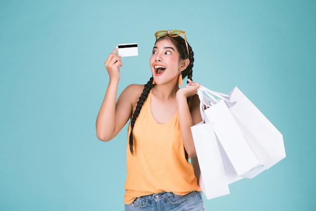 Retrato, de, jovem, morena, mulher segura, crédito, cartão, e, bolsas para compras