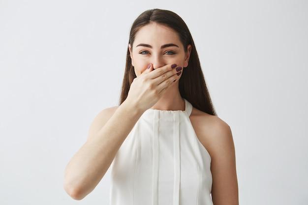 Retrato de jovem morena rindo cobrindo a boca com a mão.