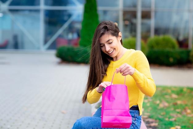 Retrato de jovem morena sentado ao ar livre no banco e olha para as sacolas de compras-de-rosa.