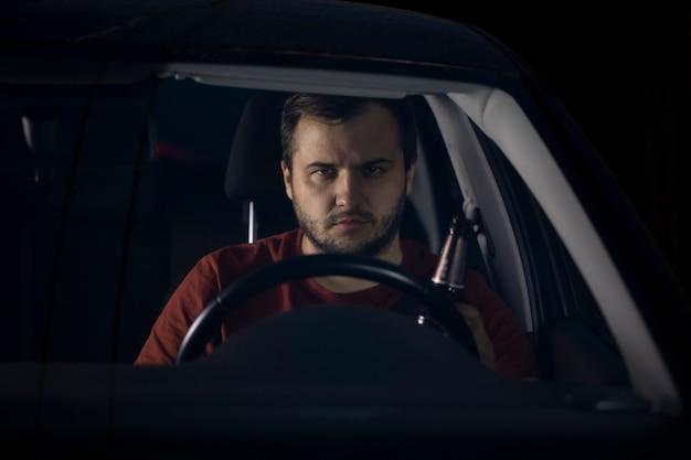 Retrato de jovem motorista bonito sentado ao volante do carro à noite