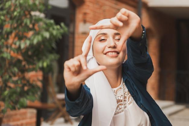 Retrato de jovem muçulmana fazendo um quadro de câmera com os dedos ao ar livre
