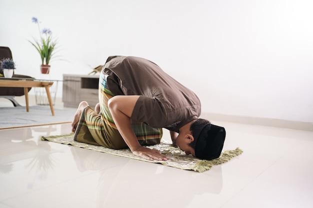 Retrato de jovem muçulmano asiático orando em casa