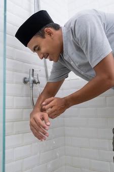 Retrato de jovem muçulmano realiza ablução (wudhu) antes da oração em casa. limpe a mão dele