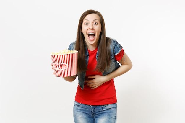 Retrato de jovem muito feliz rindo linda mulher em roupas casuais, assistindo a um filme de cinema, segurando um balde de pipoca e mantendo a mão na barriga, isolada no fundo branco. emoções no conceito de cinema.