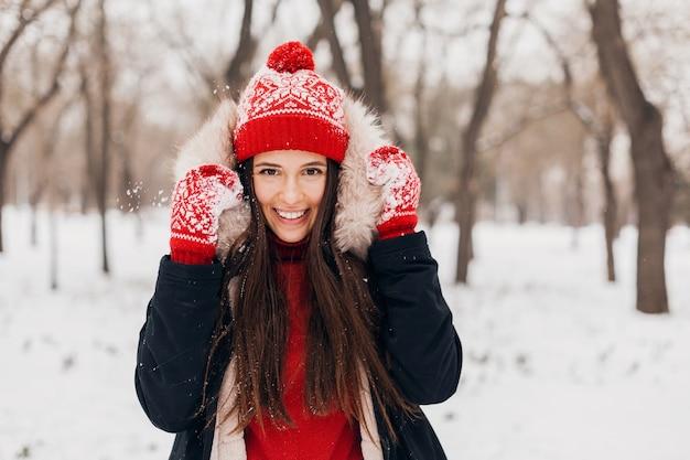 Retrato de jovem muito sorridente feliz com luvas vermelhas e chapéu de malha, vestindo um casaco de inverno, caminhando no parque na neve, roupas quentes