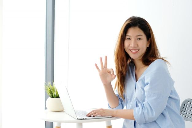 Retrato, de, jovem, mulher asian, mostrando, tá bom sinal mão, e, sorrindo, enquanto, trabalhando