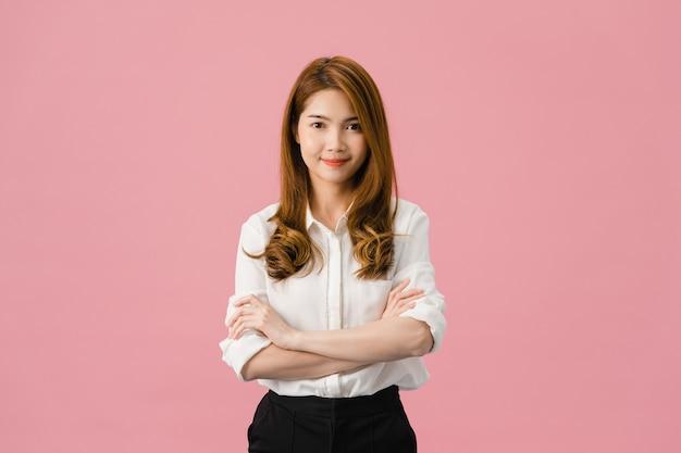 Retrato de jovem mulher asiática com expressão positiva, braços cruzados, sorriso largo, vestida com roupas casuais e olhando para a câmera sobre fundo rosa.