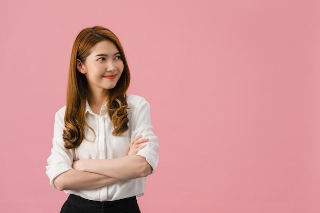 Retrato de jovem mulher asiática com expressão positiva, braços cruzados, sorriso largo, vestida com roupas casuais e olhando para o espaço sobre fundo rosa.